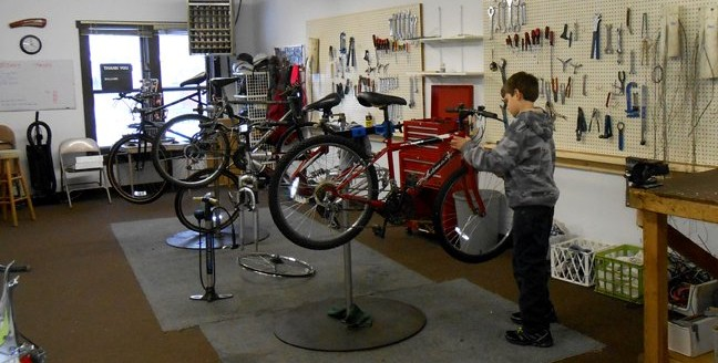 Young man works on his bicycle at the Chain Reaction Bike Shop